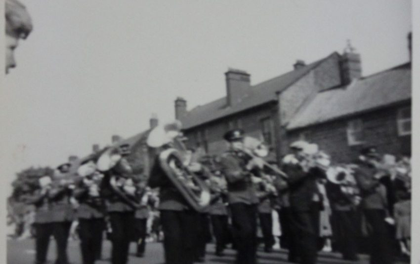A brass band performs in close formation.