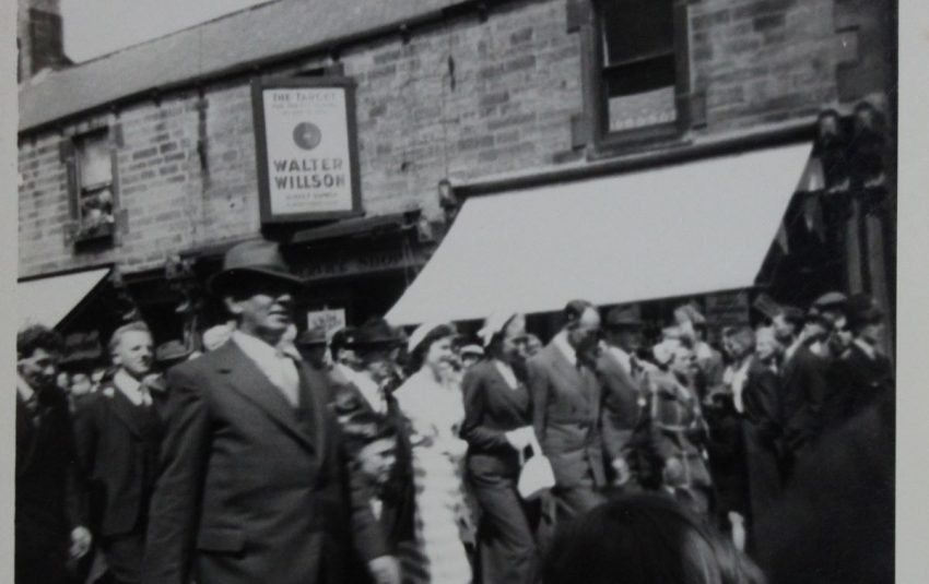 Dignitaries marching in the Picnic parade outside of Walter Wilson's shop.