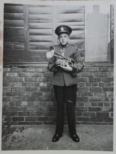 Young player, Lynn Winter Robson; posing in uniform with his instrument before the parade.