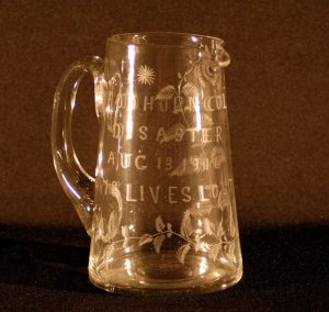 Wide bottomed glass pitcher or jug inscribed 'Woodhorn Colliery / Disaster / Aug 13 1916 / 13 lives lost'. Decorated with etched with trailing leafy plant design and a simple 16 point star.