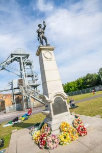 The Ashintgon Miners' Memorial statue adorned with wreaths on Picnic day, after the memorial service, at Woodhorn Museum.