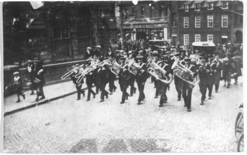Black and white photograph. A brass band performing during a parade along a cobbled street lined with on lookers. `
