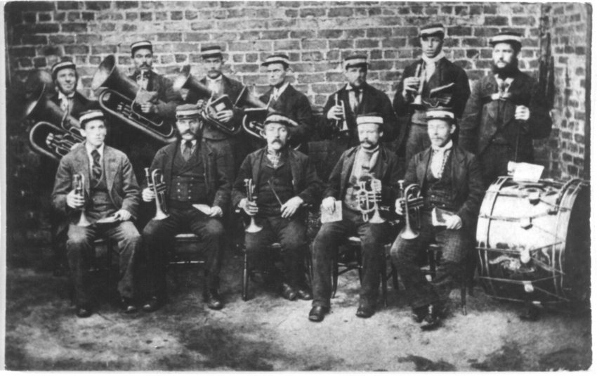 Black and white photograph. An unknown colliery band featuring a small ensemble of players. Musicians do not wear uniforms expect for simples matching caps. They are dressed in their best formal attire.