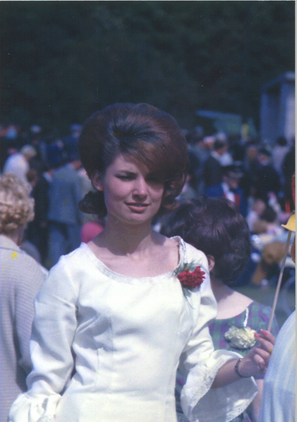 Colour photograph of a young woman in a white dress adorned with a red carnation on picnic day.