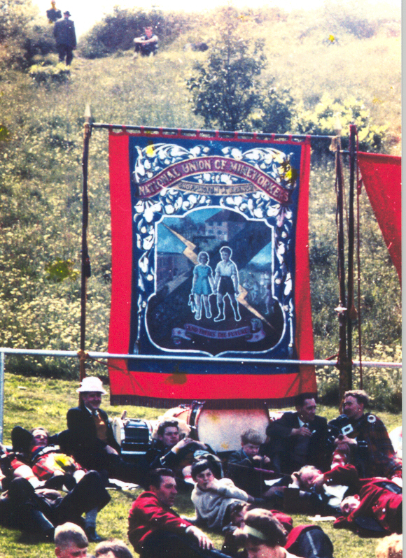 Colour photograph of a banner displayed in Atlee park with visitors and band members relaxing on the grass in front.