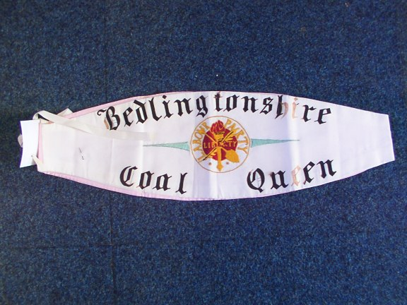 Coal Queen sash, white with black gothic lettering reads 'Bedlingtonshire Coal Queen' with an embroidered insignia in red, gold and green of the Labour Party, flaming torch crossed with shovel and quill emblazoned with the word LIBERTY.