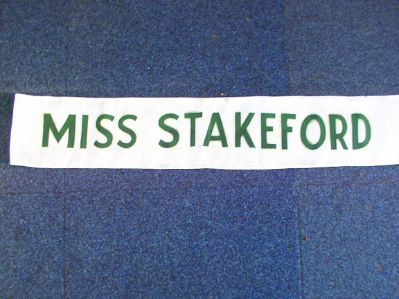Coal Queen Sash, white with green lettering reads 'MISS STAKEFORD'