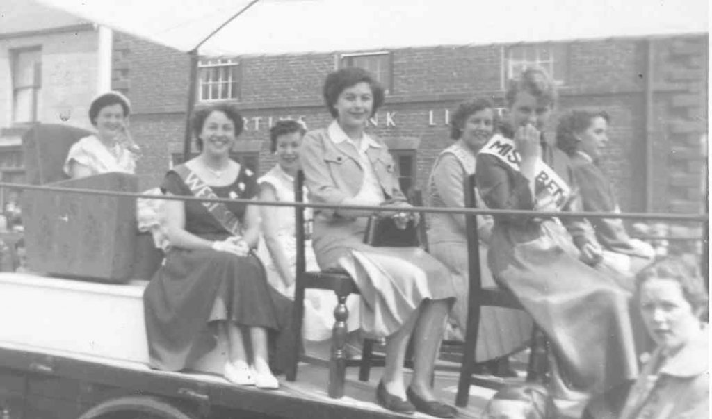 Black and white photograph of Coal Queens riding on a float on picnic day. Six local coal queens sit on wooden dining chairs on top of a slow moving float. Miss Bedlingtonshire sits on an armchair on a raised plinth at the rear of the float.