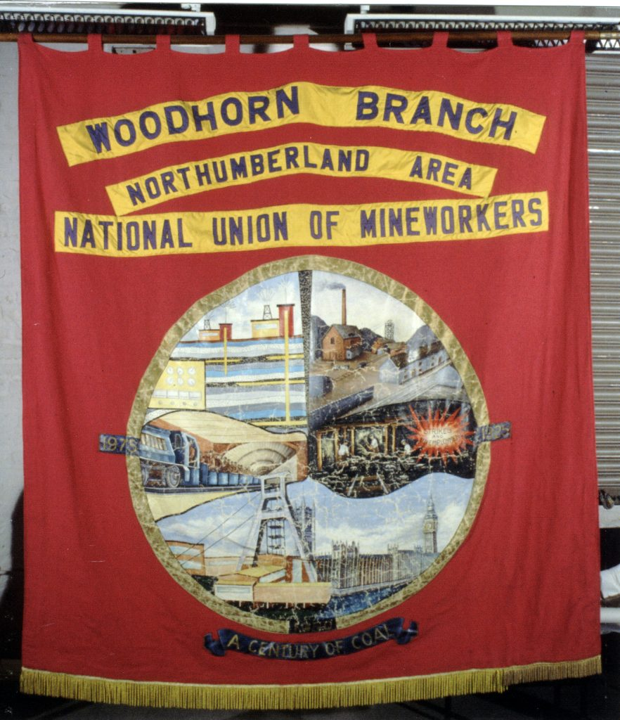 Woodhorn Colliery banner. Red silk with gold fringing. Obverse view; three yellow applique patches with blue lettering reads 'Woodhorn Branch' 'Northumberland Area' 'National Union of Mineworkers' above a central image roundel between the dates '1975' and '1925'. The roundel is divided into six pictures, from clockwise: above ground scene of a colliery, presumably Woodhorn; underground scene depicting hewers at the coal face overlaid with the words 'Strike and Unemployment' in a fireburst; the Houses of Parliament and Big Ben; unidentified industrial buildings; an underground loco carrying men ready for work; a schematic diagram showing coal seams. Beneath the roundel, words within a scroll read 'A Century of Coal'.
