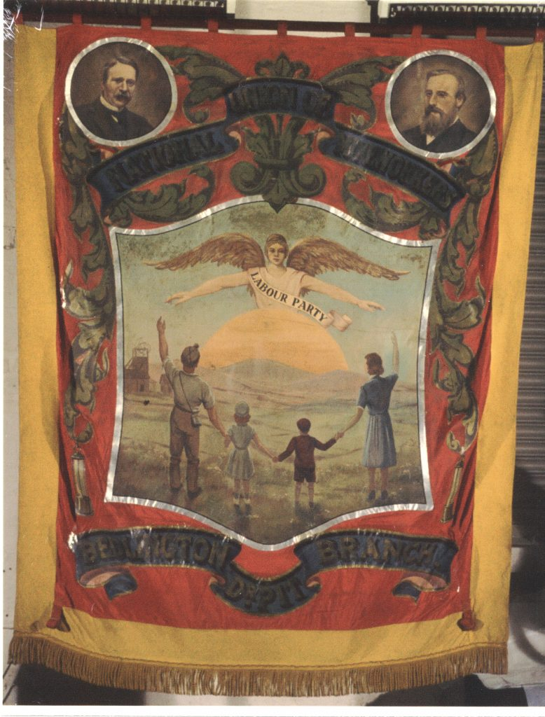 Bedlington 'Dr Pit' banner. Yellow and red silk painted banner with gold braid fringe. Obverse view: central image within a shield shows a stylised mining family in 1940s fashions (left to right, father - in miner's helmet - daughter, son and mother) in the foreground, facing rolling hills and a rising sun. Colliery buildings can be seen in the horizon to the left of the father. An angelic being with outstretched arms and wings and wearing a sash which reads 'Labour Party' sits atop the sun rise. The family stand in a line, father and mother with outstretched arms in welcome. The central image is surrounded by gold foliate designs. Additional details include two safety lamps hanging from the foliage and two roundels at the top right and left corners of the panel show male portraits. The top scroll, in blue and gold, reads 'National Union Mineworkers'. The bottom scroll reads 'Bedlington Dr Pit Branch'