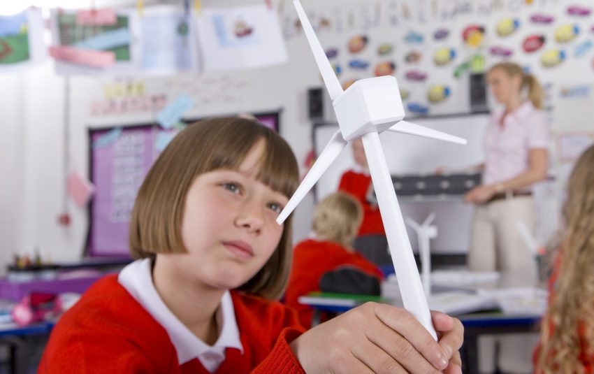 Young student looking at model of wind turbine